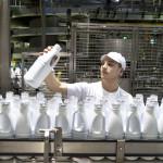 Homme chaine de bouteilles de lait usine