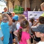 Enfants et éleveuse devant panneau pédagogique