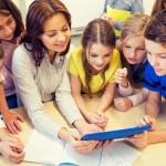 groupe d'élèves et maitresse en classe autour d'une tablette