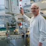 Homme technicien devant machine, chaine de yaourts