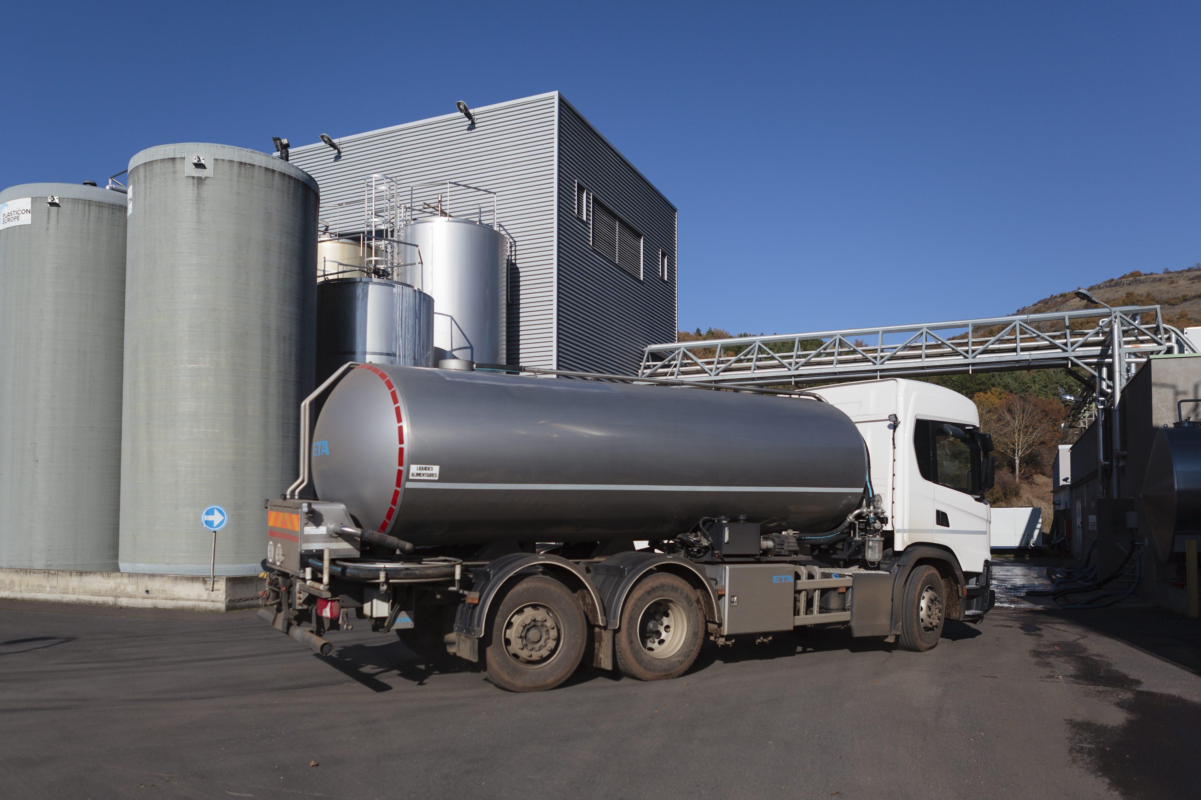 Usine, camion arrivant à l'usine, cuves