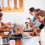 Groupe de jeunes avec ordinateur autour de table