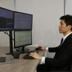 Homme devant 3 ordinateurs