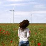 Femme de dos avec éolienne dans champ