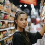 Jeune femme dans rayon de supermarché