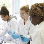 Trois lycéennes faisant expérience en laboratoire, pipette, éprouvette