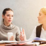 Deux femmes en formation, discussion, bureau, cahiers, réunion, marketing, travail