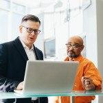Deux hommes debout devant ordinateur, discussion, bureau