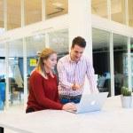 Homme et femme devant un ordinateur, debout, loft, bureau
