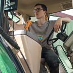 Jeune homme dans cabine de tracteur, conducteur, plan serré