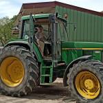 Tracteur jaune et vert avec jeune au volant, ferme