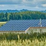 Ferme avec toit en panneaux photovoltaïques, blé, forêt