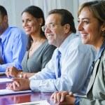 4 personnes en réunion, table, dossiers, sourires