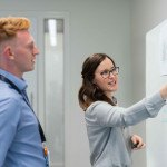Deux jeunes ingénieurs devant un tableau, étude, schéma