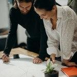 deux personnes debout qui dessinent un plan, papier blanc chemise blanche