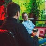 Deux jeunes assis discutent dans bureau, plantes vertes, ordinateur