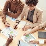 Groupe de personnes en réunion autour de graphique, ordinateur, schéma